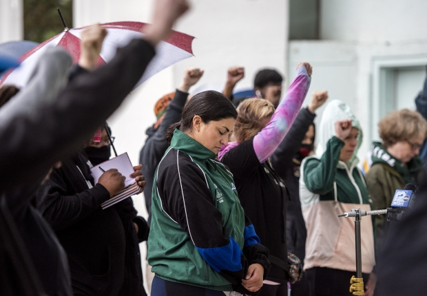 Attendees raise fists in the air during a moment of silence Sunday, May 23, 2021, at Washington Park in Milwaukee, Wis. Angela Major/WPR