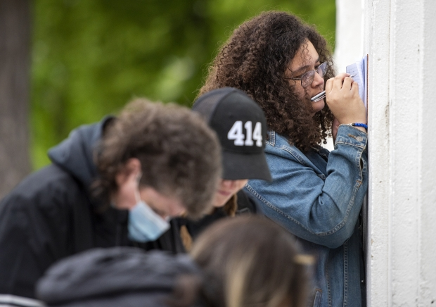 Attendees write notes for families who attended the event Sunday, May 23, 2021, in Milwaukee, Wis. Angela Major/WPR