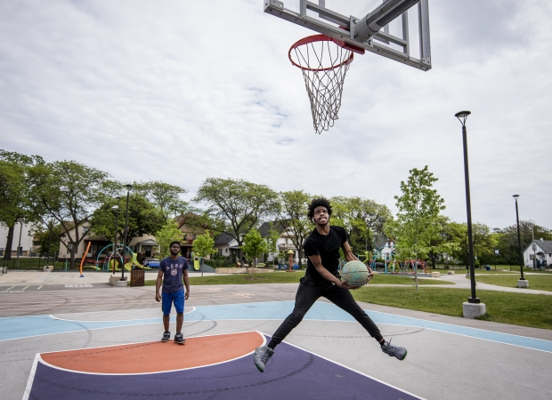 Milwaukee resident Myles Horton, right, plays basketball on a court at Columbia Playfield on Tuesday, May 25, 2021, in Milwaukee, Wis. Horton grew up playing at this park before it was renovated. Angela Major/WPR