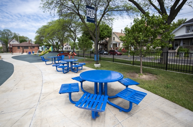 Picnic tables are located near playground equipment Tuesday, May 25, 2021, at Columbia Playfield in Milwaukee, Wis. Angela Major/WPR