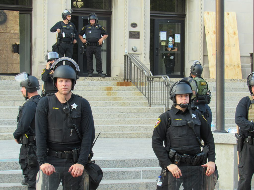 Police watch as protesters gather on August 24th, 2020 in Kenosha. (Photo by Isiah Holmes)Police watch as protesters gather on August 24th, 2020 in Kenosha. Photo by Isiah Holmes/Wisconsin Examiner.