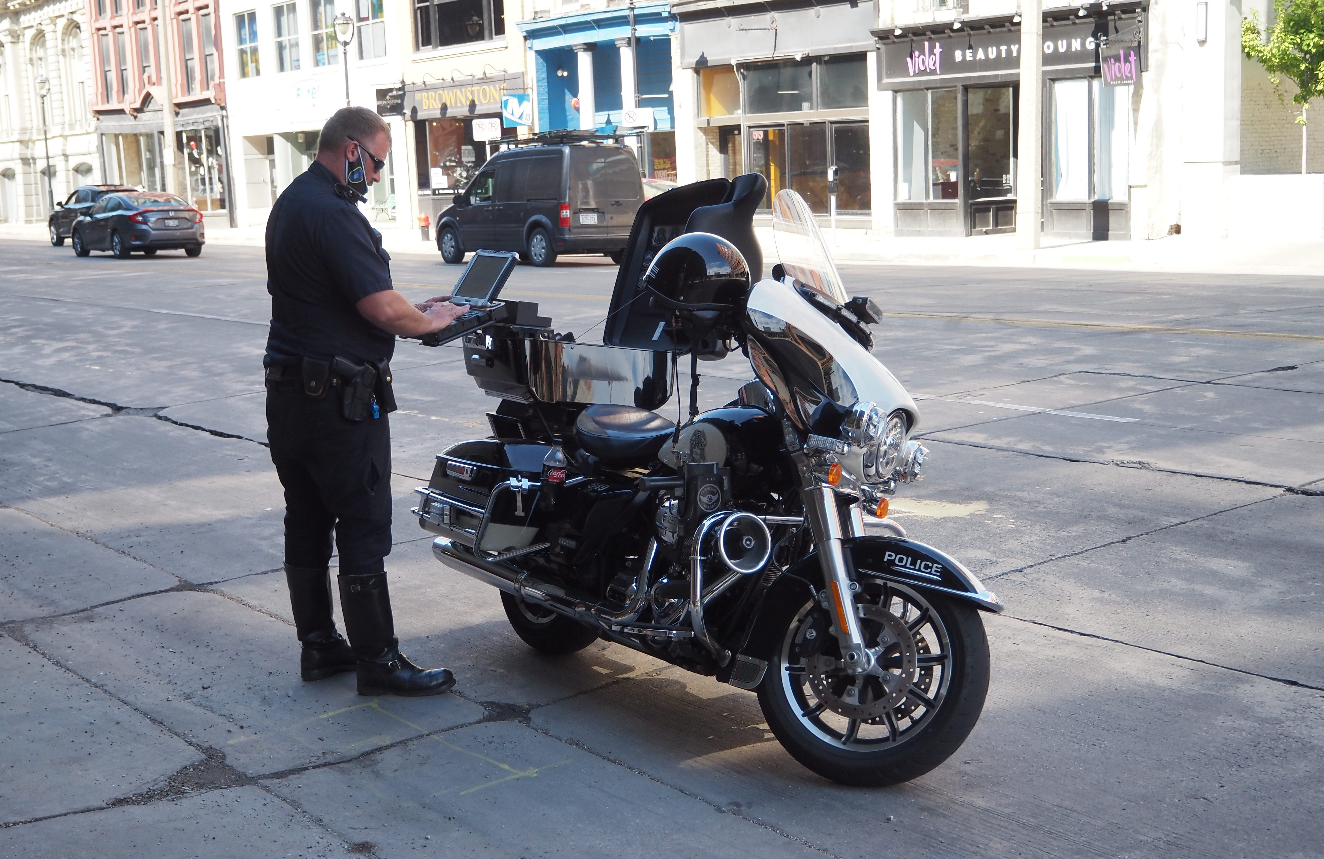 A Milwaukee Police Department officer enters a report into a laptop after a traffic stop. Photo by Jeramey Jannene.