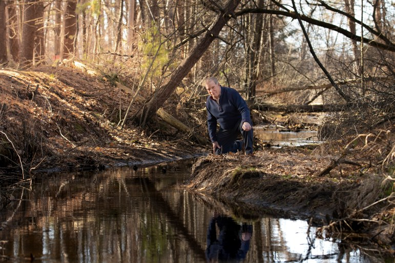 Jeff Lamont, a Marinette, Wis., resident and retired hydrologist, is seen next to a creek where it empties into Lake Michigan's Green Bay. This creek is the most highly PFAS-contaminated of all the tributaries that empty into the lake based on a recent study funded by The Sea Grant Institute. Sampling occurred at all significant tributaries from the eastern shores of Green Bay at the north end of Door County, Wis., to Escanaba, Mich. Credit: Mike Erhart for The Midwest Center for Investigative Reporting