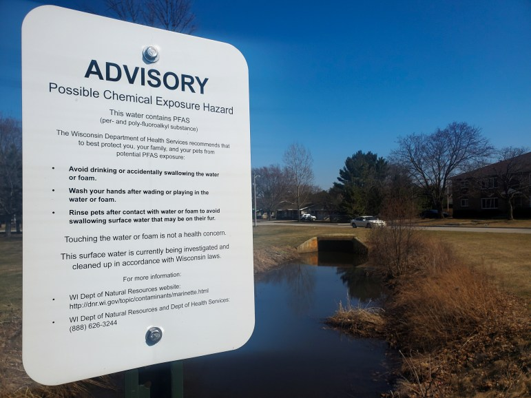 Signs posted along a ditch running through a southern Marinette, Wis., neighborhood warn against exposure to the forever chemicals known as PFAS on April 5, 2021. (John McCracken for The Midwest Center for Investigative Reporting)