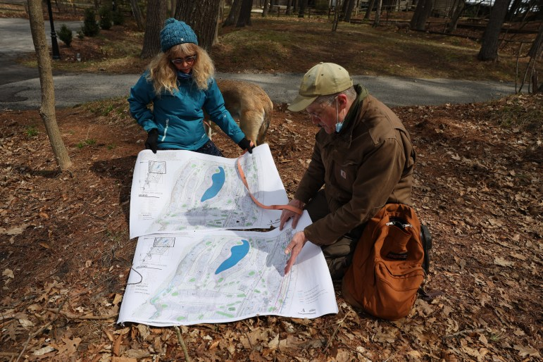 Belle Ragins and Erik Thelen, who live near the site of Kohler Co.'s proposed golf course in Sheboygan, Wis., examine a map prepared by environmental engineer Roger Miller, who chairs the town of Wilson Plan Commission. The map overlays the project with present lake levels, showing several planned features under water due to erosion and fluctuating water levels along Lake Michigan's shoreline. Photo taken April 27, 2021. Credit: Dee J. Hall / Wisconsin Watch