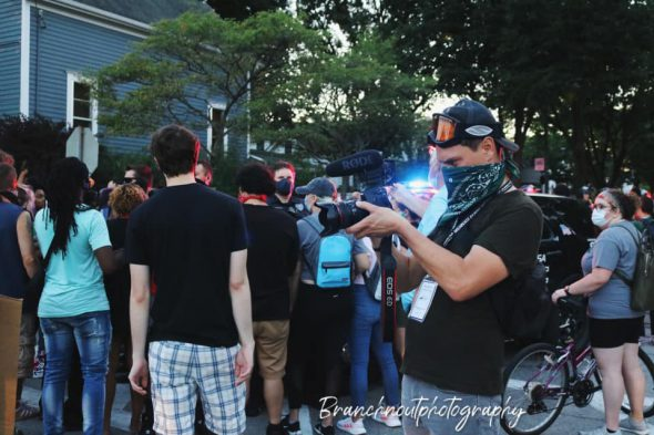 Sean Kafer filming the protestors forming a humane chain around a police vehicle after a fellow protestor is arrested. Photography credit to Teaya Branch Wauwatosa, WI, August 15th, 2020.