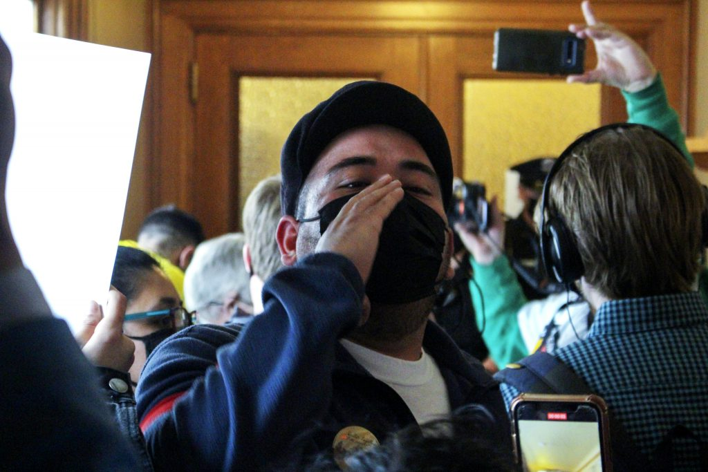 A protester leads a chant against removing pro-immigrant measures from the state budget. Photo by Henry Redman/Wisconsin Examiner.