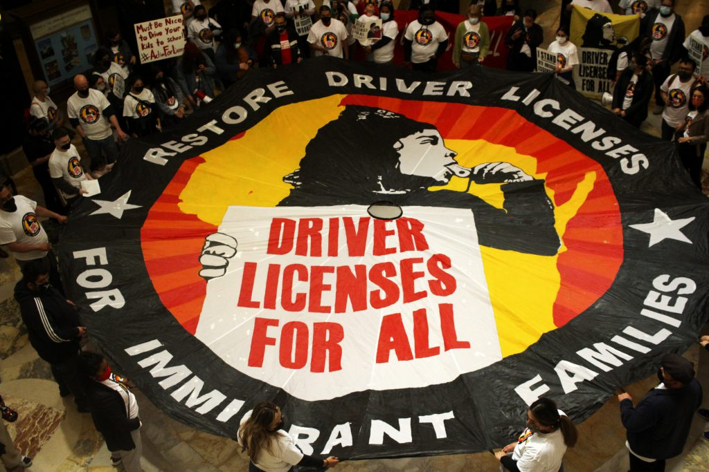 Immigration activists unveil a banner in the Capitol rotunda. Photo by Henry Redman/Wisconsin Examiner.
