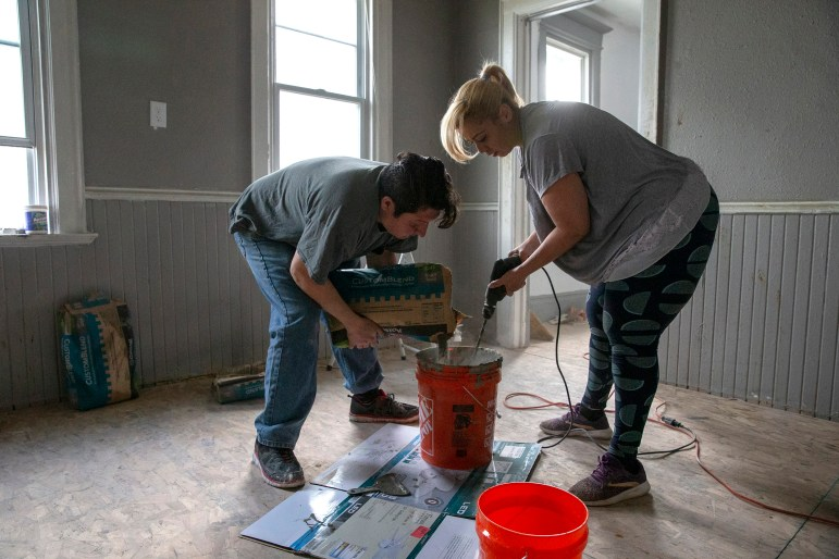 Sheila DeCuavas, right, and her husband, Nabor Cuevas Tirado, mix concrete for tiles in their new house on May 13, 2020. Decuavas and Cuevas Tirado worked for at least four months to fix the house. Credit: Zhihan Huang / Milwaukee Journal Sentinel