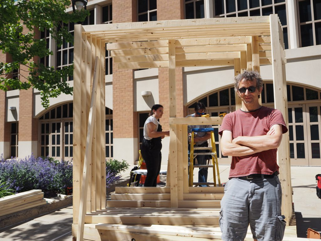 Artist Matthias Neumann standing in front of his newest art piece for Sculpture Milwaukee. Photo by Hope Moses.