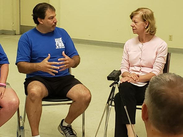 Mike Gackstatter speaks with Sen. Tammy Baldwin during a round table on Wednesday for workers who face layoff at Hufcor in Janesville. Photo by Erik Gunn/Wisconsin Examiner.