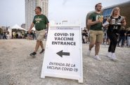 Fans walk past a sign advertising COVID-19 vaccines Tuesday, July 20, 2021, outside the Fiserv Forum in Milwaukee, Wis. Angela Major/WPR