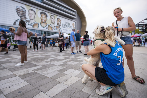 Mary Merg hugs her dog, Tucker, as they walk around the market Wednesday, July 28, 2021, at the Deer District in Milwaukee, Wis. Angela Major/WPR