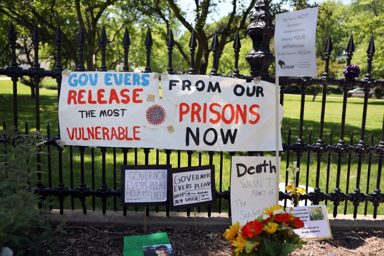 """Signs and posters outside the Wisconsin governor's mansion in Maple Bluff, Wis., on June 18, 2020, are part of a """"Drive to Decarcerate"""" event. Those attending urged Gov. Tony Evers to release inmates from Wisconsin's overcrowded prisons to slow the spread of COVID-19. A range of other actions ultimately eased crowding in jails and prisons during the pandemic, but advocates say the state has a long way to go toward addressing crowding more broadly. One out of every two inmates in Wisconsin's prisons has tested positive for the virus, a rate four times higher than the state's general population. Credit: Coburn Dukehart / Wisconsin Watch"""