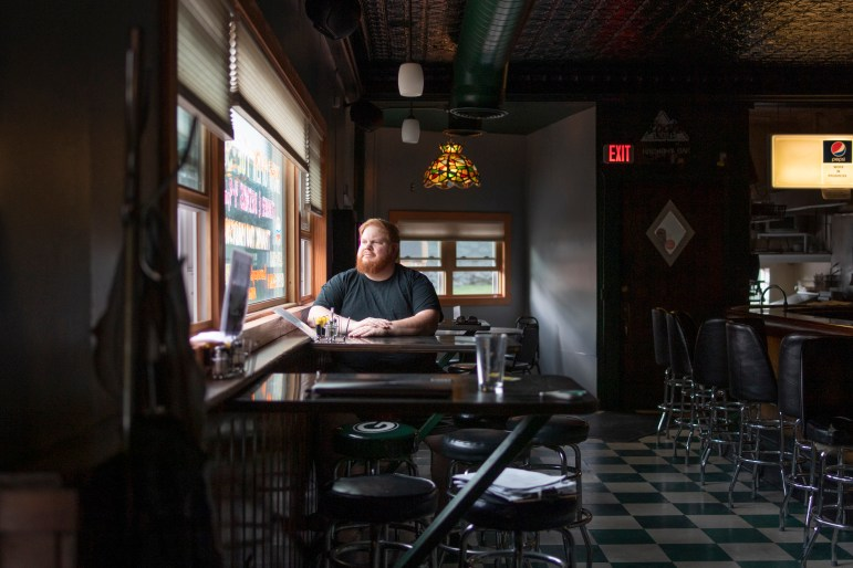 Jamie McPeters, 44, is seen at Harmony Bar and Grill in Madison, Wis., on June 28, 2021, where he works one shift a week. After losing work during the COVID-19 pandemic, McPeters says he will leave the industry after 20-plus years to pursue a graphic design career. McPeters says he won't miss the low wages — or occasionally rude clientele. He says trying to enforce mask-wearing during the pandemic was a challenge. Credit: Isaac Wasserman / Wisconsin Watch
