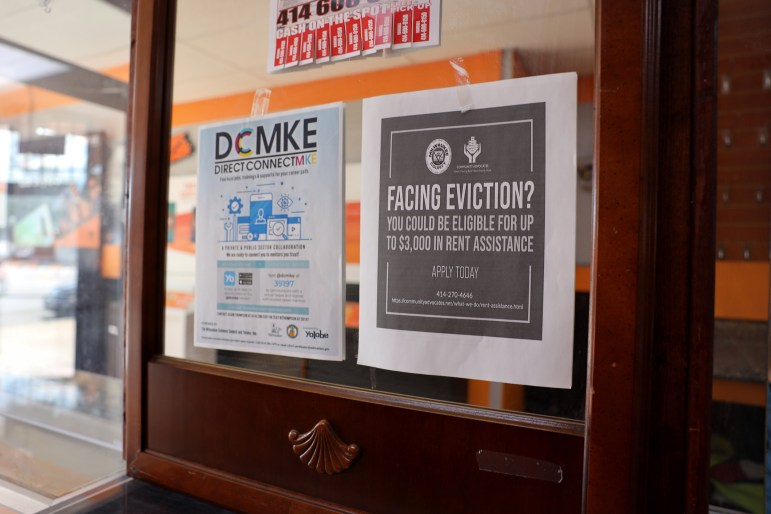 A sign inside a Boost Mobile store on Milwaukee's Atkinson Avenue encourages renters facing eviction to call Community Advocates to apply for emergency rental aid. Photo taken Sept. 4, 2020. Photo by Coburn Dukehart / Wisconsin Watch