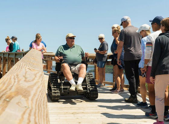 The public can now reach the top of the Eagle Tower at Peninsula State Park using the 100 tower stairs or the 850-foot fully accessible canopy walk shown here. Accessible equipment, like this reservable all-terrain wheelchair from Access Ability Wisconsin, make the outdoors an option for all. / Photo Credit: Wisconsin DNR