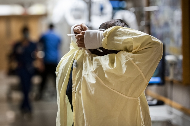 A healthcare worker ties a medical gown before caring for a patient who has COVID-19 on Tuesday, Nov. 17, 2020, at UW Hospital. Angela Major/WPR