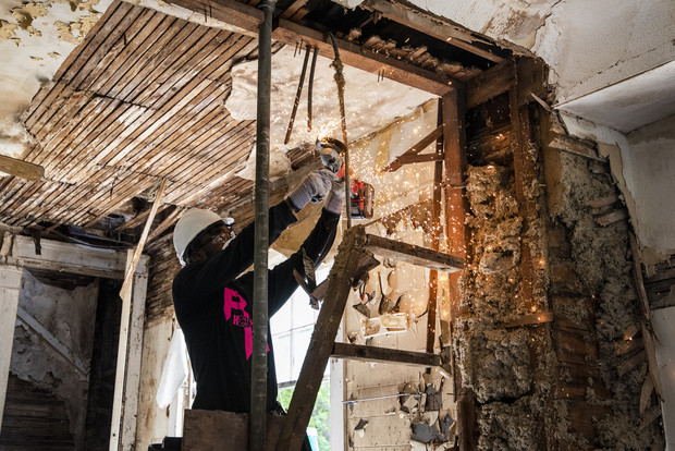 A worker deconstructs elements of a kitchen inside a home that will soon be remodeled for new owners Thursday, Aug. 5, 2021, in Milwaukee, Wis. Angela Major/WPR