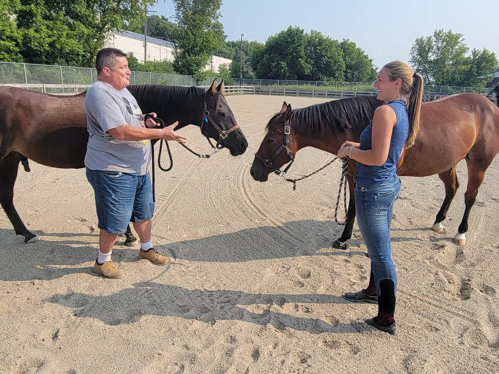 Army veteran Glenn Scheuermam and Felicia Sackett, farm manager and equine specialist at MKE Urban Stables, take horse co-therapists Coy and Coco out for some exercise. Photo by Edgar Mendez/NNS.