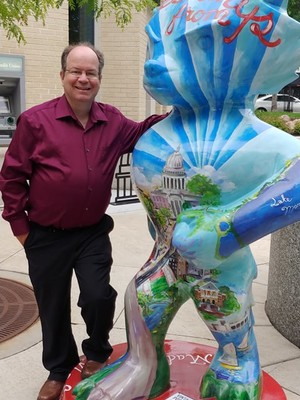 Pete Loerke poses on the Capitol Square in Madison next to a Bucky Badger statue in this 2018 photo. The Madison man is hesitant to call out people who post pandemic misinformation even though he wishes more people would get vaccinated against COVID-19. Photo courtesy of Pete Loerke/WPR.