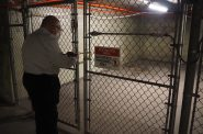 Sam Denny locks a gate to a tunnel in the Schlitz Park complex. Photo by Jeramey Jannene.