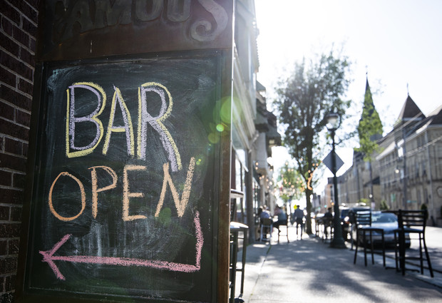 A sign on East Brady Street in Milwaukee indicates that a bar is open to customers on Monday, July 13, 2020. Angela Major/WPR