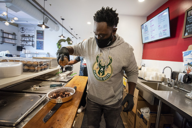 Jason Alston, owner of Heavens Table BBQ, works behind the counter Friday, Sept. 24, 2021, in Milwaukee, Wis. Alston received a pardon from Gov. Tony Evers on April 2, 2021. Angela Major/WPR