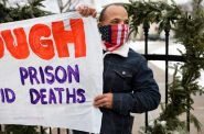"""Ramiah Whiteside of Milwaukee holds a sign during a protest against the spread of COVID-19 in Wisconsin prisons outside of the governor's mansion in Maple Bluff, Wis., on Nov. 24, 2020. Whiteside, who is formerly incarcerated, calls Wisconsin's highest-in-the-nation rate of imprisoning Black residents """"a slap in the face."""" Whiteside works for Milwaukee-based EXPO, which advocates for formerly incarcerated people. Coburn Dukehart / Wisconsin Watch"""